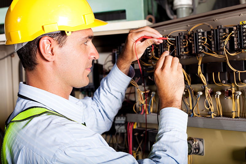 Electrician busy with a maintenance work. Building services.