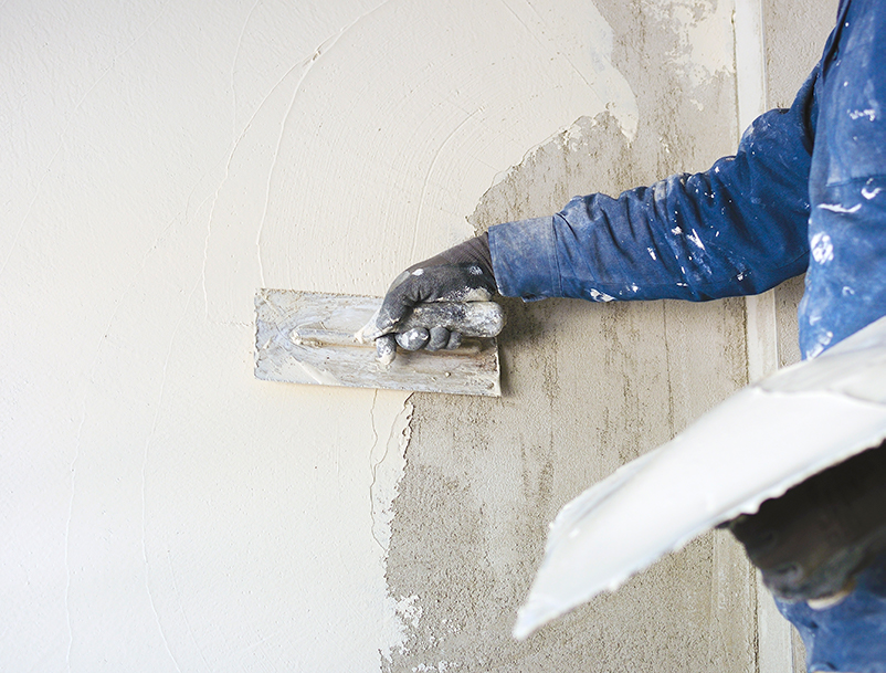 Man plastering a wall. Part of building services by Studio Charrette.